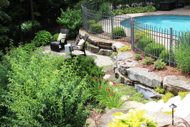 Aménagement paysager champêtre cour arrière pierre naturelle espace détente et piscine creusée
