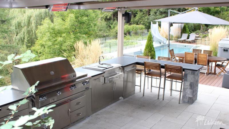 Cuisine extérieure dotée d'un comptoir granite et d'un comptoir bar sous la pergola et le chauffe-terrasse